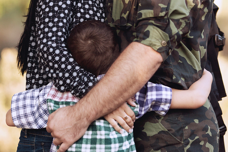 soldier and family hugging