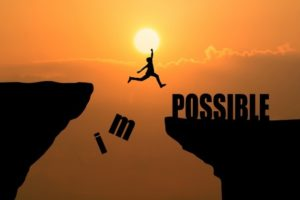 """person jumping across crevasse knocking the """"im"""" off of the word impossible"""