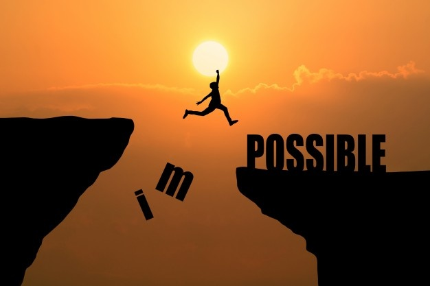 "person jumping across crevasse knocking the ""im"" off of the word impossible"